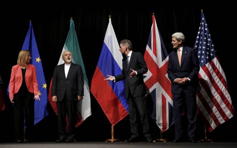 L'ancien secrétaire d'État américain John Kerry (droite), l'ex-secrétaire aux Affaires étrangères britannique Philip Hammond (2e à droite) et Federica Mogherini (G) parlent avec le ministre des Affaires étrangères iranien Mohammad Javad Zarif, au Centre international de Vienne, en Autriche, le 14 juillet 2015, pendant les négociations autour de l'accord de Vienne sur le nucléaire iranien. Carlos Barria/Reuters