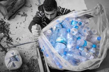 Jamil, réfugié syrien de 40 ans et volontaire ouvrier à L'Écoute, soulève le contenu d'une benne de tri sélectif dans une école publique de Beyrouth.